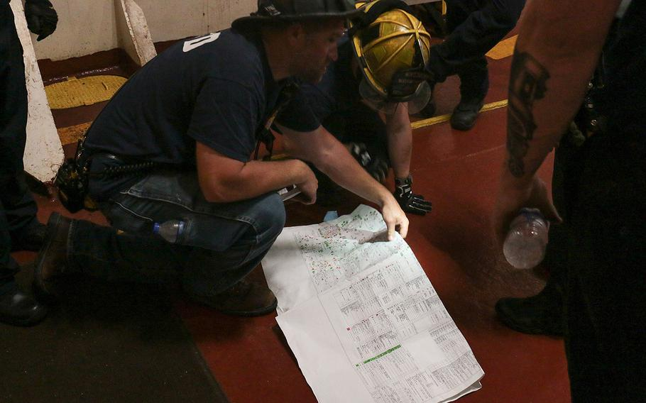 Part of the training at the 27th annual Marine Firefighting School in Norfolk, Va., was teaching firefighters the complexities of maneuvering around the cramped corridors and gangways of a naval vessel. Here, firefighters go on a hunt aboard the docked cargo ship Cape Rise on May 17, 2018.
