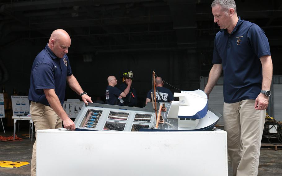 Coast Guard Chief Warrant Officers Rob Birdwell, left, and David Porco, came to Norfolk, Va., from their training center in Coast Guard Training Center Yorktown, Va., to teach firefighters about the unique challenges of keeping a ship afloat while fighting a massive fire on it. Here, they demonstrate that on a model at the 27th annual Marine Firefighting School held May 14-19 in Norfolk.