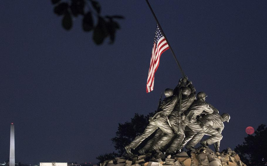The flag on the U.S. Marine Corps War Memorial in Arlington, Va., is at half staff in honor of the late Sen. John McCain, R-Ariz., as the moon rises on August 26, 2018.