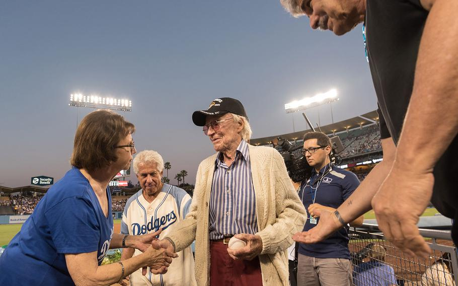Fans shake hands with Sam Folsom at Dodger Stadium in Los Angeles on Aug. 14, 2018 after the 98-year-old World War II Marine Corps veteran was honored by the team.