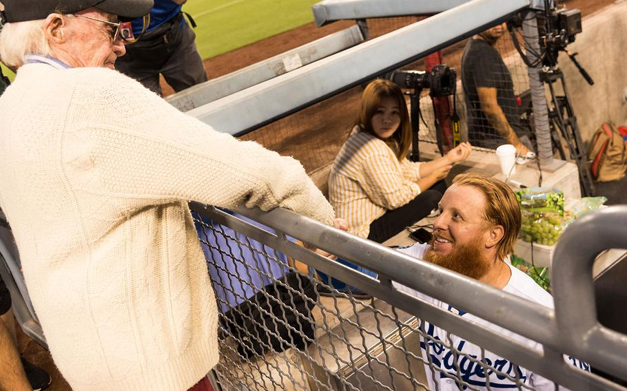 Los Angeles Dodgers star third baseman Justin Turner shakes hands with 98-year-old Marine veteran Sam Folsom in the middle of the second inning during a game against the San Francisco Giants on Aug. 14, 2018.