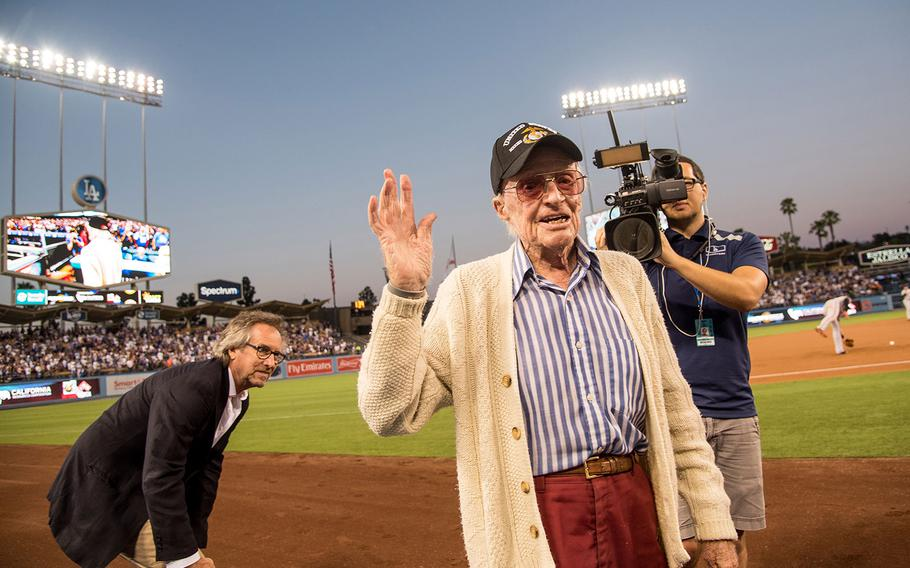Marine veteran Sam Folsom, 98, a fighter pilot who shot down three Japanese planes during the Battle of Guadalcanal in World War II, later served in the Korean War and retired as lieutenant colonel waves to the crowd at Dodger Stadium in Los Angeles on Aug. 14, 2018 as his son, Gerrit Folsom, left, looks on. The Dodgers honored Folsom, who lives in nearby Santa Monica, Calif., as their Hero of the Game.