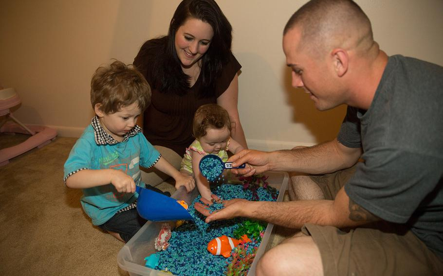 Emmett, Brooke, Emma Lynn and Cpl. Preston Fouch play with toys in Emmett's sensory room May 8, 2014. Emmett was diagnosed with Autism Spectrum Disorder in July 2013. TRICARE is currently evaluating treatment therapy options for children with autism.