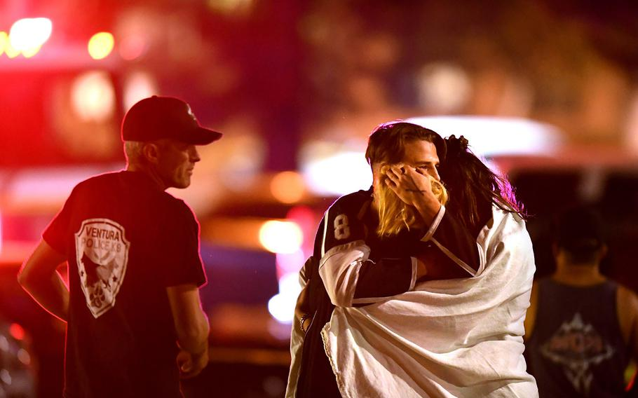 People comfort each other after a mass shooting at the Borderline Bar & Grill in Thousand Oaks, Calif., late Wednesday night, Nov. 7, 2018. The shooter has been identified as a 28-year-old Marine Corps veteran who apparently killed himself after killing a dozen people.