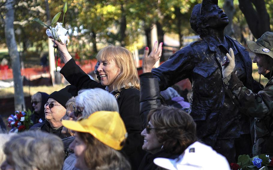 Janis Nark of Aspen, Colo., holds up flowers during a group photo at the Vietnam Women's Memorial on Sunday, Nov. 11, 2018. About 60 Vietnam nurses traveled from across the country to attend the event, which marked 25 years since the memorial was established on the National Mall.