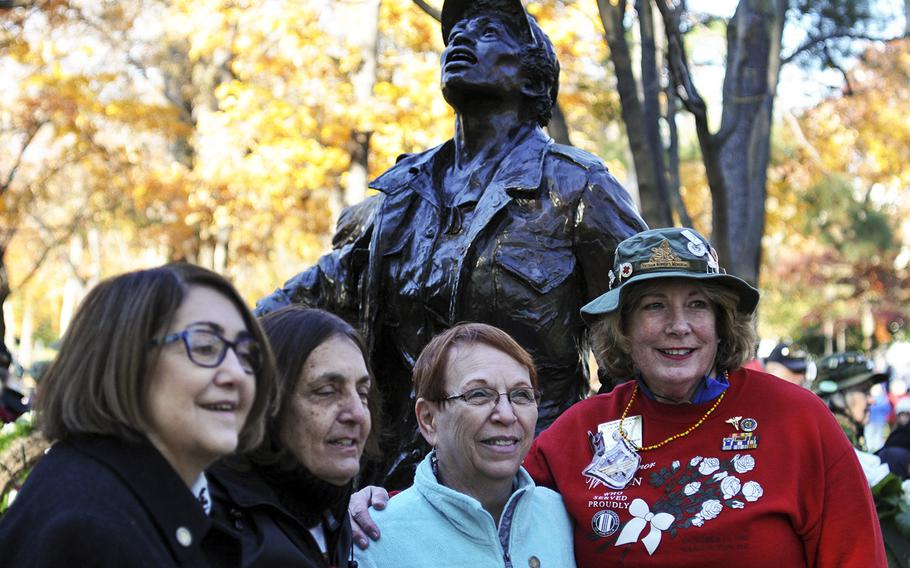 Women pose in front of the Vietnam Women's Memorial following a Veterans Day ceremony on Sunday, Nov. 11, 2018. About 60 Vietnam nurses traveled from across the country to attend the event, which marked 25 years since the memorial was established on the National Mall.