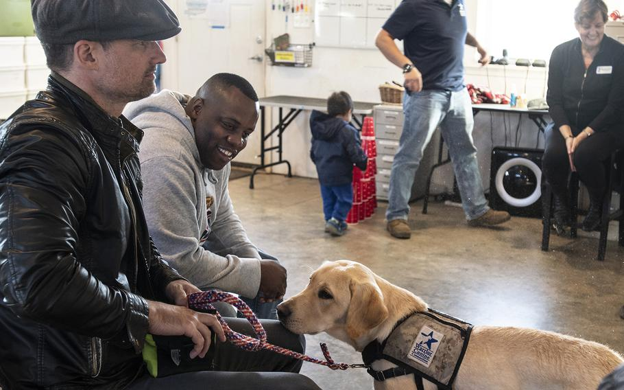 """Actor Warren Christie, left, and military consultant Jamel Daniels, right, part of the cast of the new TV show """"The Village,"""" visit Warrior Canine Connection in Boyds, Maryland, on November 10, 2018, to learn about service dogs and their role helping veterans. The show will air in 2019."""