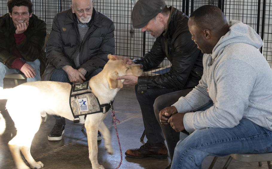 """Cast of the new TV show """"The Village"""" visit Warrior Canine Connection in Boyds, Maryland, on November 10, 2018, to learn about service dogs and their role helping veterans. The show will air in 2019. From left to right: actors Daren Kagasoff, Dominic Chianese and Warren Christie and military consultant Jamel Daniels."""