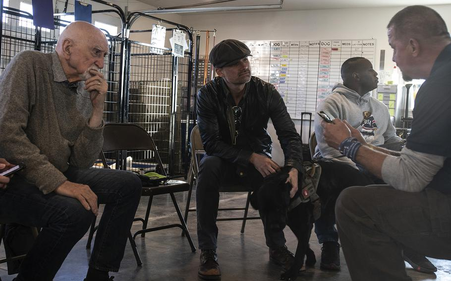 """Actors Dominic Chianese (left) and Warren Christie (center), cast of the new TV show """"The Village,"""" visit Warrior Canine Connection in Boyds, Maryland, on November 10, 2018, to learn about service dogs and their role helping veterans. The show will air in 2019. (Meredith Tibbetts/Stars and Stripes)"""