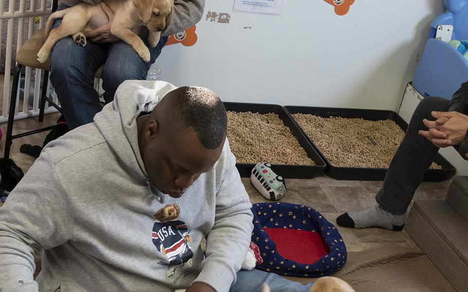 """Military consultant Jamel Daniels, foreground, part of the cast of the new TV show """"The Village,"""" visits Warrior Canine Connection in Boyds, Maryland, on November 10, 2018, to learn about service dogs and their role helping veterans. The show will air in 2019. Seated is actor Dominic Chianese, known for his roles in """"Sopranos"""" and """"The Godfather Part II."""""""