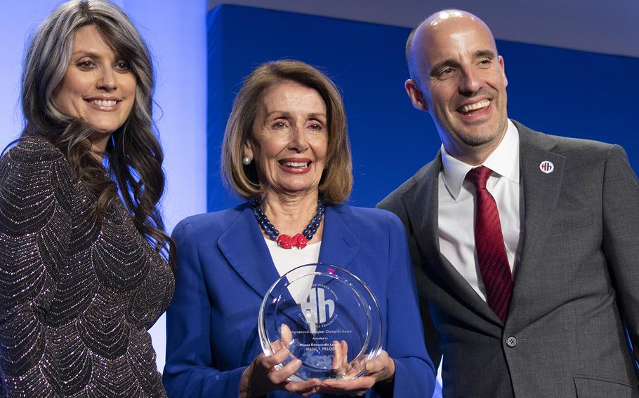 House Minority Leader Nancy Pelosi, D-Calif., center, is presented with the Congressional Caregiver Champion Award by military caregiver Nikki Stephens and Steve Schwab, executive director of the Elizabeth Dole Foundation, during the foundation's Heroes and History Makers event in Washington, D.C., Nov. 29, 2018.