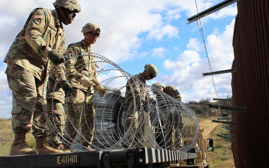 Engineers from 937th Clearance Company prepare to place concertina wire on the Arizona-Mexico border wall, Dec. 1, 2018.