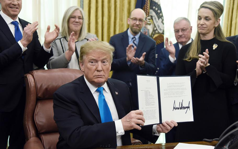 President Donald Trump holds a signed directive centralizing all military space functions under a new Space Force, in the Oval Office of the White House on February 19, 2019.