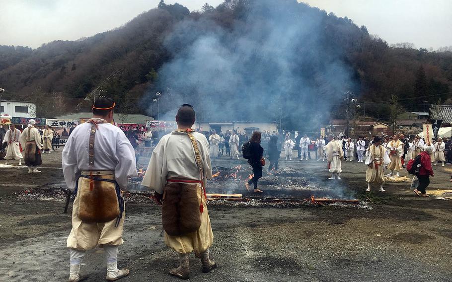 People walk over hot embers during the Hiwatari Matsuri at Mount Takao, Japan, Sunday, March 10, 2019.