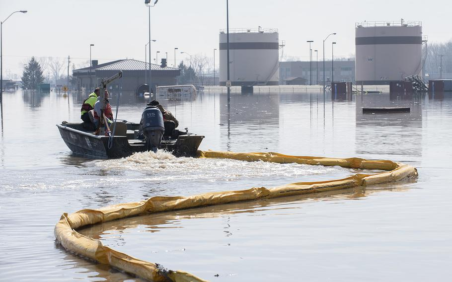 Contracted employees deploy a spill containment boom around the Offutt Air Force Base fuel storage area as a precautionary measure March 18, 2019 following flooding of the southeast portion of the base.