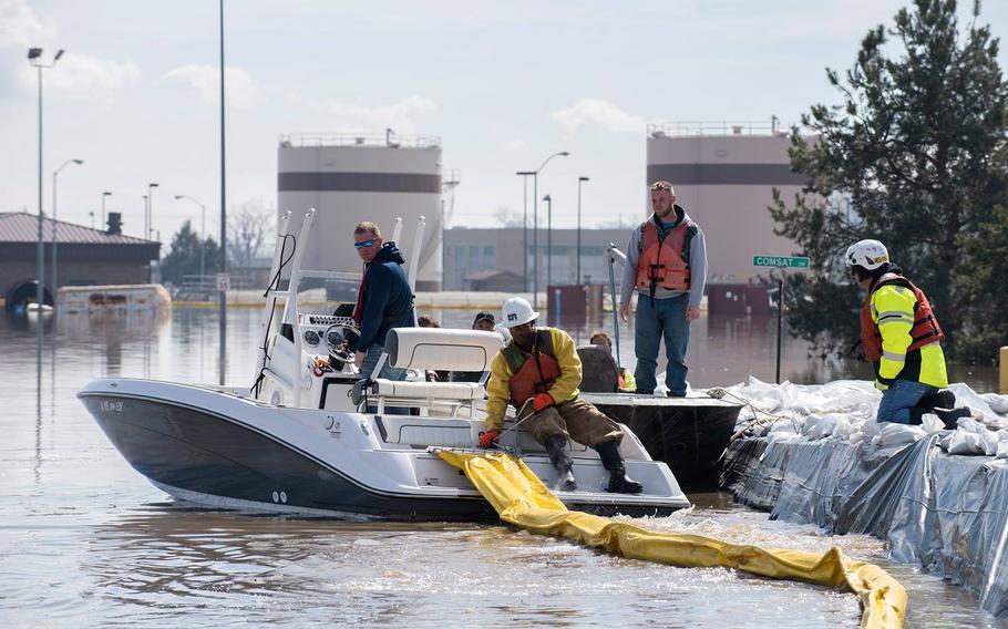 Personnel help assess damage at Offutt Air Force Base in Nebraska after major flooding.