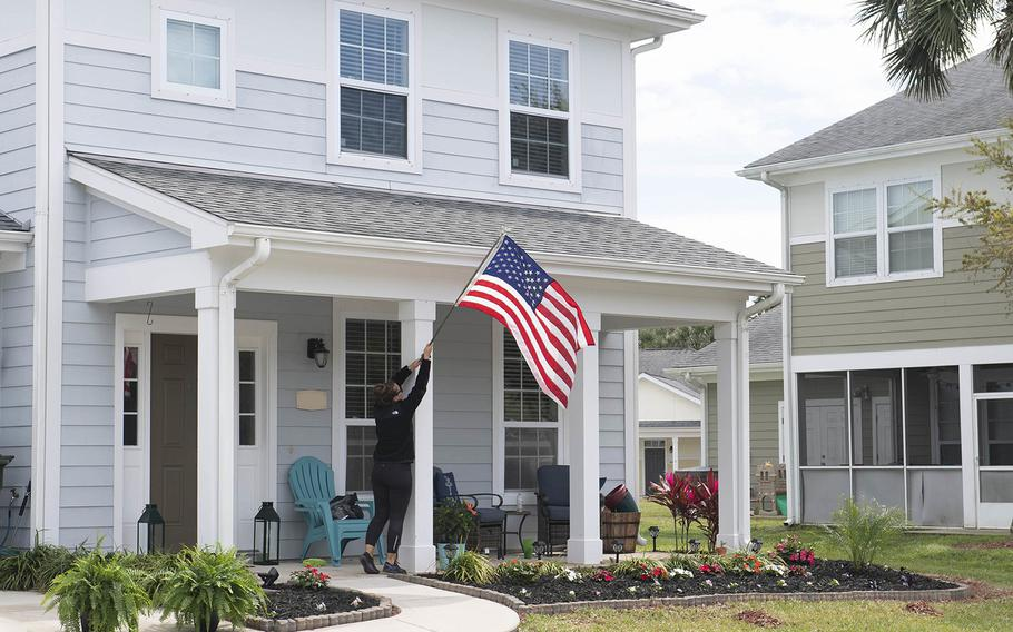 A resident at Balfour Beatty Housing raises the American flag at her home at an on-base military housing community at Naval Station Mayport, Fla., on March 18, 2019.