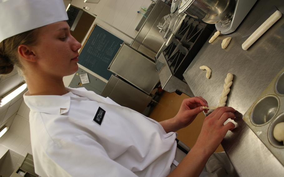 Pvt. Kayle Witzman, an Army food service specialist, prepares hot rolls at Fort Lee, Va.