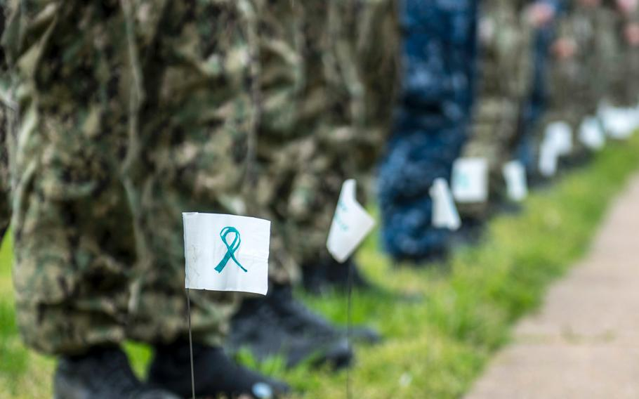 Sailors assigned to the aircraft carrier USS George H.W. Bush stand next to flags with encouraging messages during a kickoff event for Sexual Assault Awareness and Prevention Month.