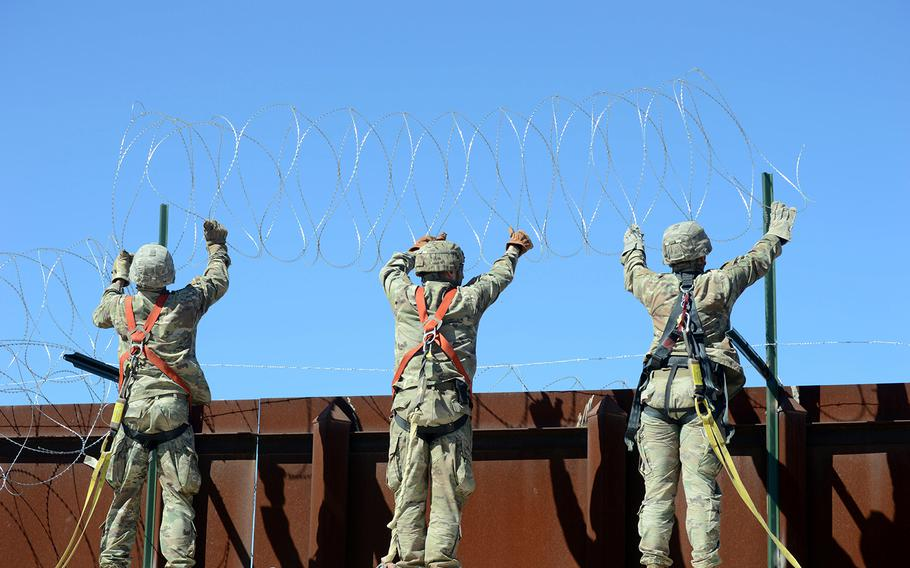 A team of soldiers with 610th Engineer Support Company attach a string of concertina wire to the border fence at San Luis, Ariz., on March 14, 2019.