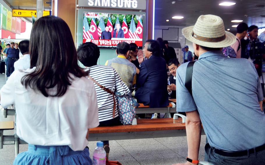 People at watch television coverage of the historic summit between President Donald Trump and North Korean leader Kim Jong Un at Seoul Station in South Korea, Tuesday, June 12, 2018.