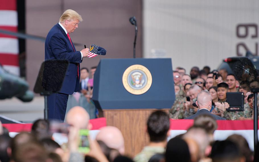 President Donald Trump autographs a servicemember's hat following his speech to servicemembers and families on Osan Air Base, South Korea, Sunday, June 30, 2019.