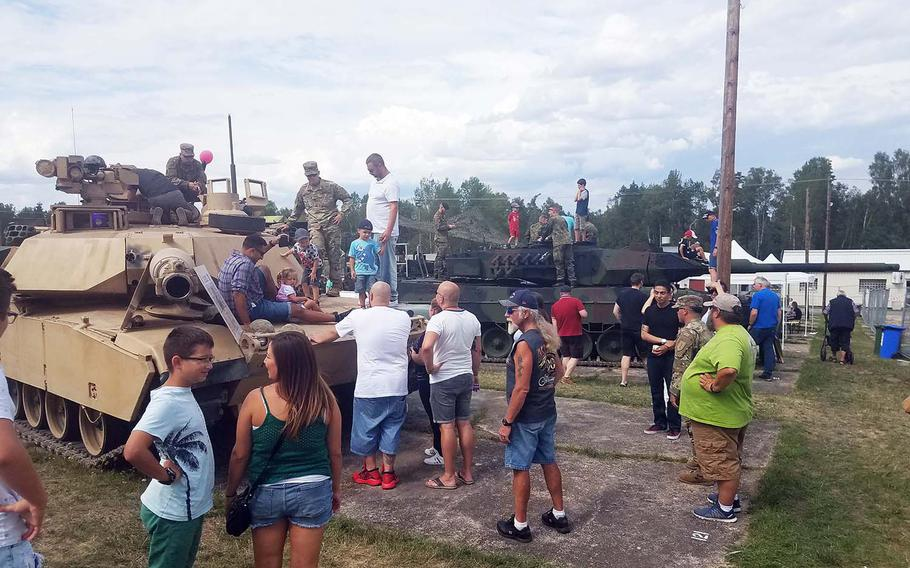 German and American families explore U.S. Army and Bundeswehr tanks at the German American Volksfest at Grafenwoehr, Germany, Friday, Aug. 2, 2019.