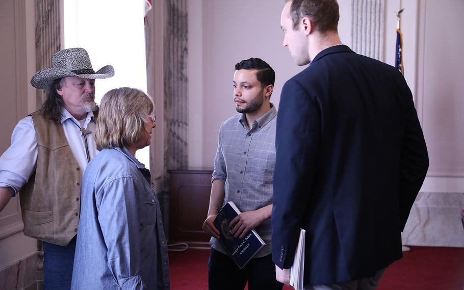 Donna Ellis Cornell, daughter of Sgt. 1st Class Melvin Hatt, speaks to two senate aides March 15, 2019, at the Russell Senate Building while her husband, Robert Cornell, far left, looks on.