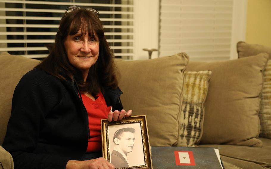 Kimberly Steinman-Elmquist holds a portrait of her father Sgt. John Karibo at a home in Washington, D.C. March 15, 2019.