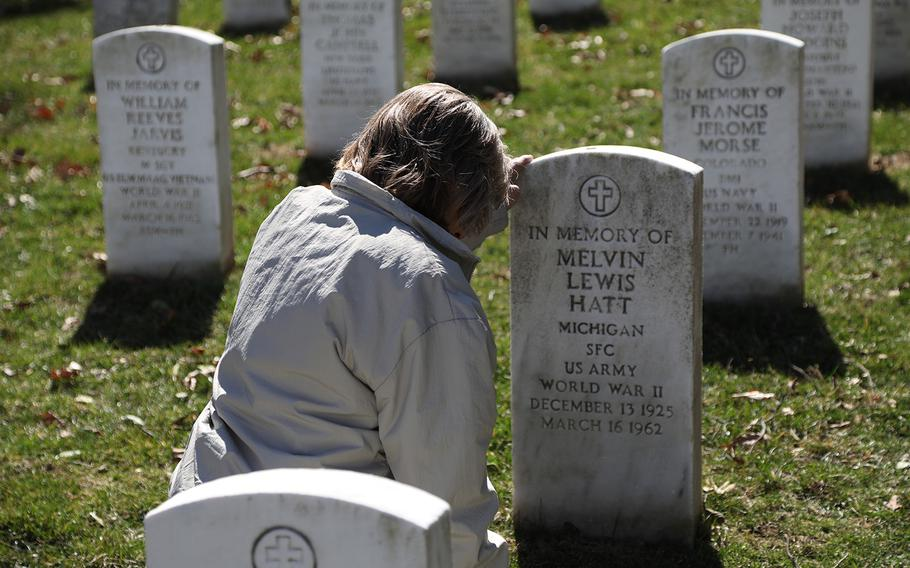 Donna Ellis Cornell, daughter of Sgt. 1st Class Melvin Hatt, kneels before a headstone in Arlington National Cemetery that was placed in memory of her father, March 17, 2019. She learned just the night before that her grandmother had requested the headstone.