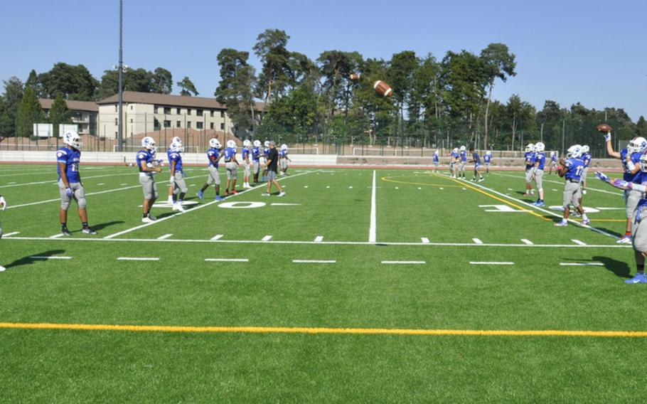 Ramstein Royals players toss balls back and forth on the team's new football field Friday, Aug. 23, 2019, at Ramstein Air Base. The new field and accompanying lights will allow the program to play Friday night home games after years of Saturday afternoon action.
