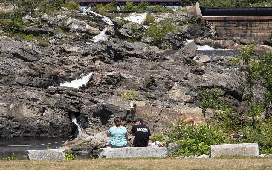 Two visitors to Veterans Memorial Park in Lewiston, Maine, in August, 2019 sit on benches overlooking the Androscoggin River's Great Falls.