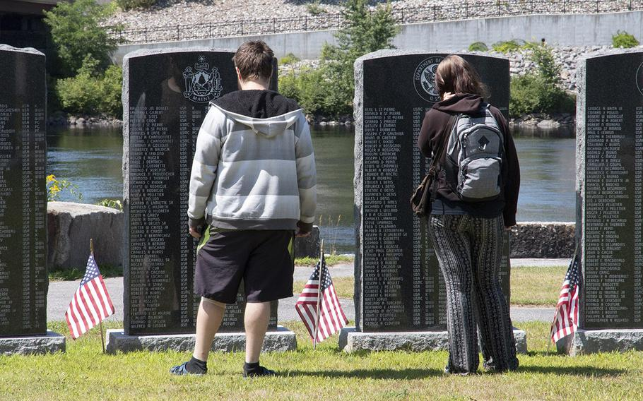 Visitors to the Veterans Memorial Park in Lewiston, Maine, in August, 2019, read the names on stones listing local veterans.