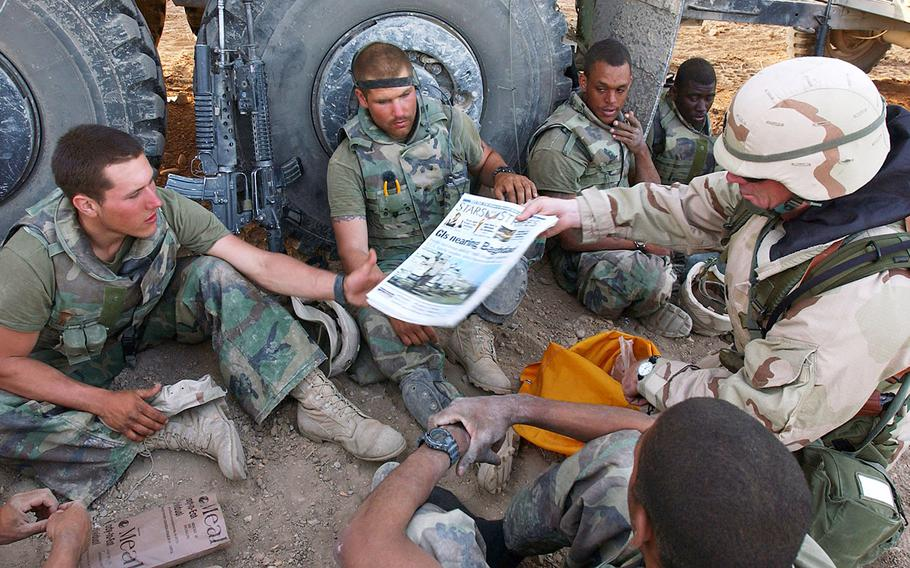In a 2003 photo, Command Sgt. Maj. John Sparks delivers copies of Stars and Stripes to U.S. Marines from Weapons Platoon, 3-2 India Company. The Marines were part of Task Force Tarawa, deployed in support of Operation Iraqi Freedom.