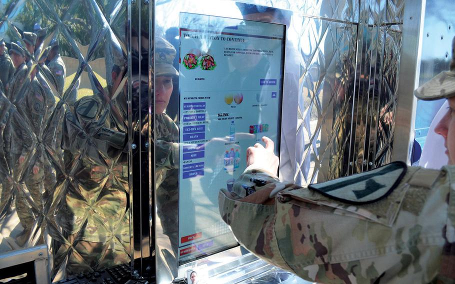 Staff Sgt. Victoria Corona orders a burrito from the touchscreen menu of the Culinary Outpost food truck Feb. 6, 2020, at Fort Hood, Texas. The truck is the Army's sixth and the first to offer a Tex-Mex menu.