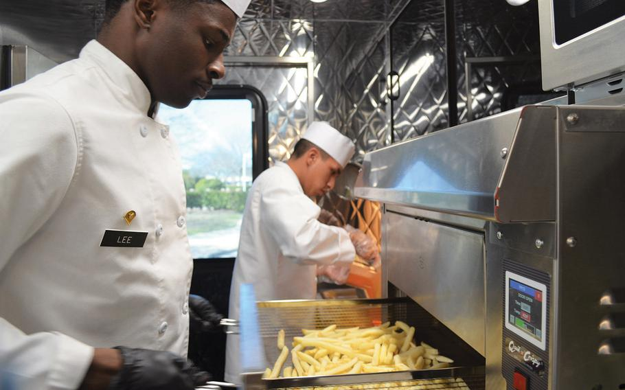 Spc. Isiah Lee checks on fries as they cook in an air fryer on the Culinary Outpost food truck Feb. 6, 2020, at Fort Hood, Texas. As part of the Army's initiative to offer soldiers healthier meal options, the food trucks do not have traditional grease fryers.