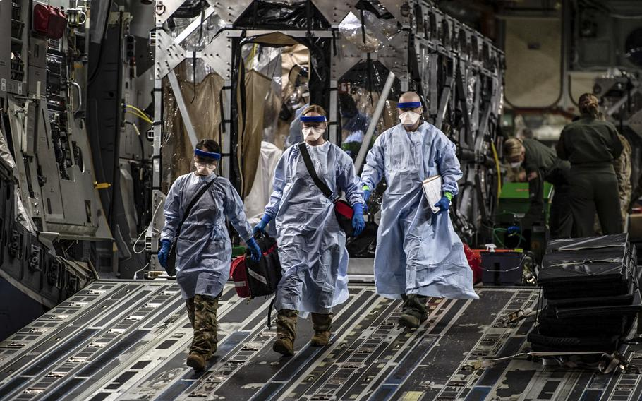 Three medical airmen exit a C-17 Globemaster III aircraft at Ramstein Air Base, Germany, April 10, 2020, following the first-ever operational use of the Transport Isolation System. The TIS is an infectious disease containment unit designed to minimize contamination risk to aircrew and medical attendants while allowing in-flight medical care for patients with an infectious disease -- in this case, COVID-19.