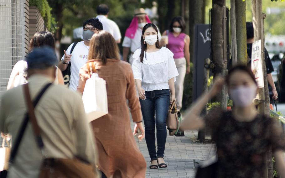 People wear masks while strolling through the Omotesando district of central Tokyo, Aug. 14, 2020.