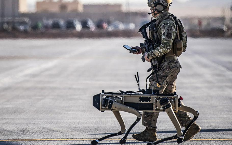 Tech. Sgt. John Rodriguez, 321st Contingency Response Squadron security team, patrols with a Ghost Robotics Vision 60 prototype during an exercise at Nellis Air Force Base, Nev., Sept. 3, 2020. Air Force scientists are exploring how humans will interact with artificial intelligence systems when they behave independently.
