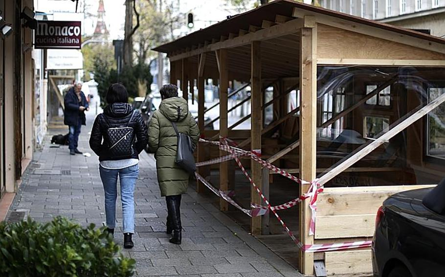 People pass a closed restaurant during the temporary closing of restaurants and bars as the spread of coronavirus continues in Munich, Germany, on Wednesday.