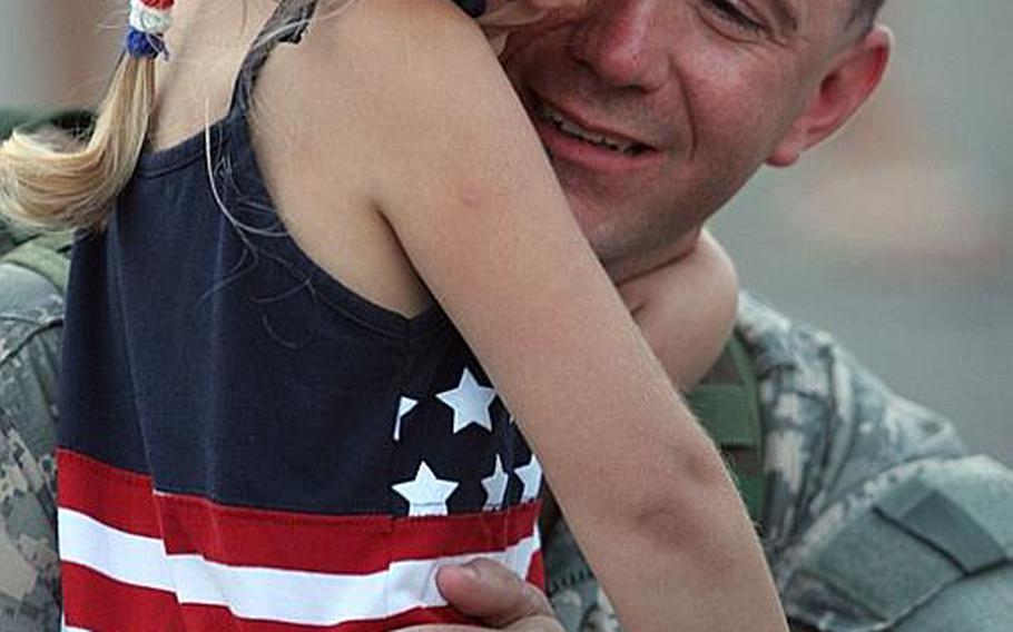 Sgt. 1st Class Kevin Brown, of Morrisville, Vt., hugs his daughter 5-year-old daughter, Lauren, as he and other members of the Vermont National Guard's Task Force Saber returned home after 11 months in Ramadi, Iraq, Thursday, June 15, 2006, at the National Guard hangar at Burlington International Airport in Burlington, Vt. Six members of the unit were killed during the deployment.