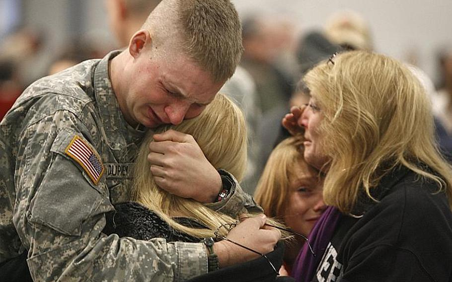 Pfc. Troy Duprey, left, of White River Junction, Vt., hugs his fiance, Tiffany Knapp, as his mother, Gloria, hugs his brother, Josh, before a deployment ceremony in Essex Junction, Vt., Friday, Jan. 8, 2010. Two hundred more Afghanistan-bound troops from the Vermont National Guard are shipping out. They are members of a special training unit of the 86th Infantry Brigade Combat Team based in Rutland.
