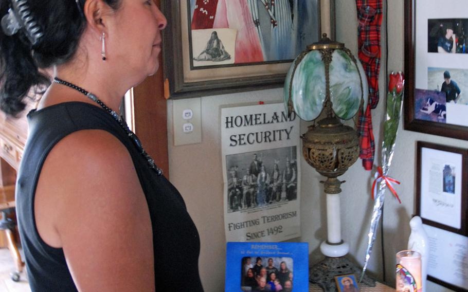 Looking at her family's memorial wall of photos in her Phoenix home, Jeanette Baker prays for her son, Army Sgt. Jonathan Hughey, who committed suicide Jan. 1. She turned to her Catholic faith to help her get through her grief as she searches for answers to why her son killed himself.