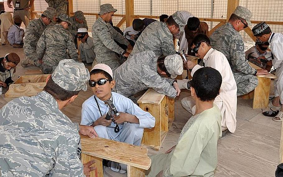Boys from Kandahar, Afghanistan, learn how to build a shelf with help from the U.S. Air Force earlier this year. In the absence of civilian aid workers, the U.S. military must deviate from fighting to take on humanitarian and community building jobs.