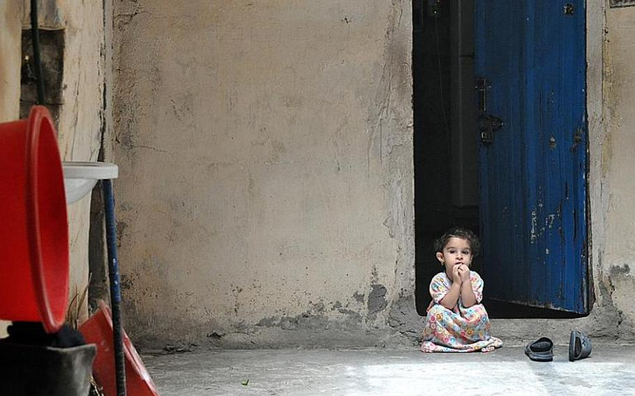 Little Bdoor, sits in the doorway of the room she lives in, in downtown Baghdad.
