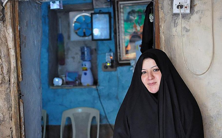 Aklas Farhood, who was widowed when her husband was killed in a Baghdad bombing, stands in front of the tiny room that she lives in with her two sons.