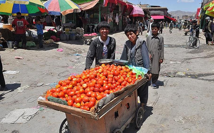 Children push a cart of tomatoes in the Kabul Fruit Market on June 9.  Vendors complain that they must pay bribes to government officials to stay in business.