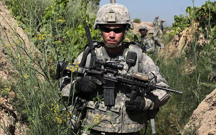 Sgt. Mitchel Stallings, of Troop B, 1st Squadron, 71st Cavalry Regiment, and other troops move through an irrigation trench in a grape orchard in Dand district, Kandahar province, Afghanistan on June 19.