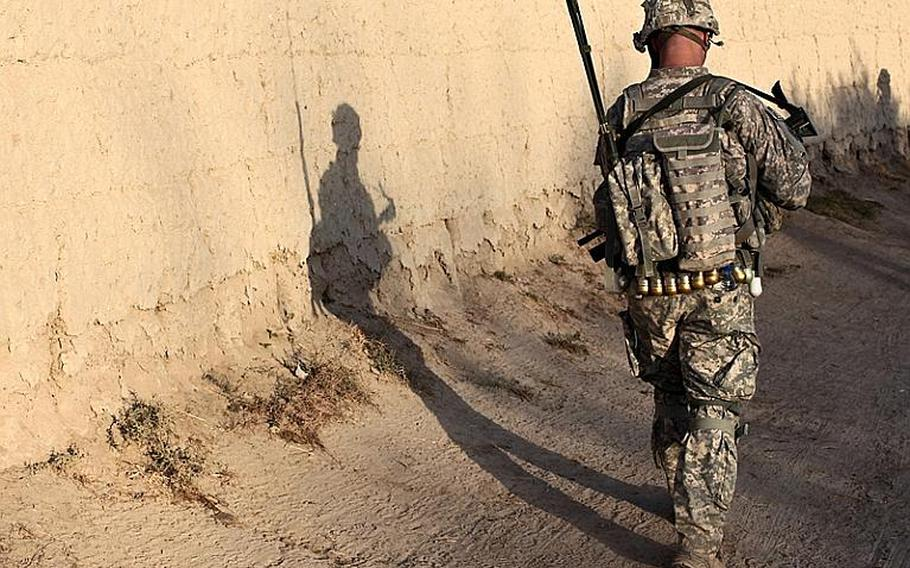 Shadows are cast on a mud wall as soldiers from Company D, 1st Battalion, 22nd Infantry head out on an early morning patrol in the Malajat area of Kandahar, Afghanistan on Oct. 4.
