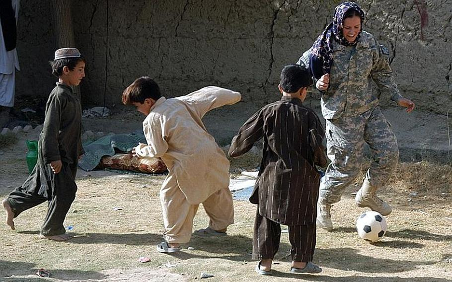 Second Lt. Randy Wintermantel plays soccer with some of the children of Robat, a village in southern Afghanistan, during a visit there by U.S. soldiers. The soldiers handed out book bags to students in the nearby school, and female soldiers were shown how to make flat bread by some of the Afghan women of Robat.
